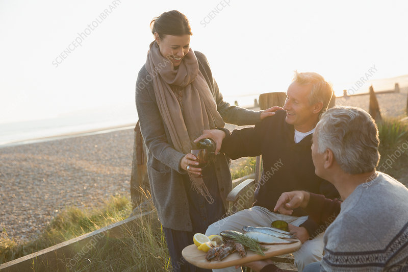 Mature friends drinking wine and enjoying barbecue