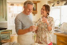Smiling mature couple drinking wine and cooking