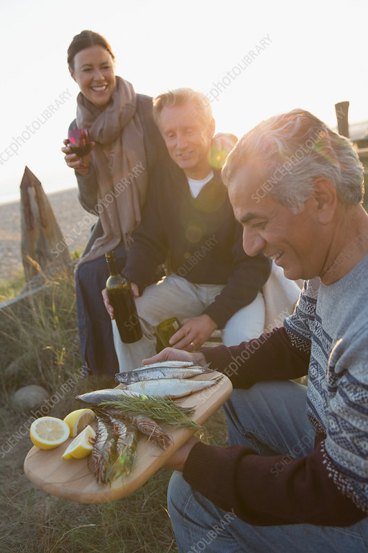 Mature friends drinking wine and barbecuing fish