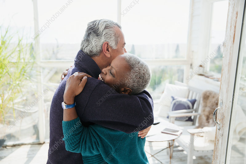 Affectionate senior couple hugging on sun porch