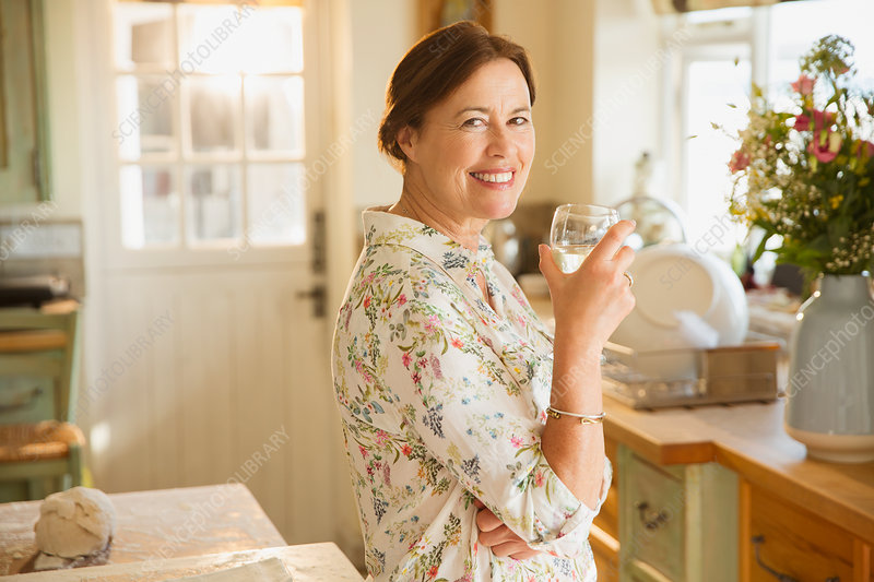 Portrait mature woman drinking wine in kitchen
