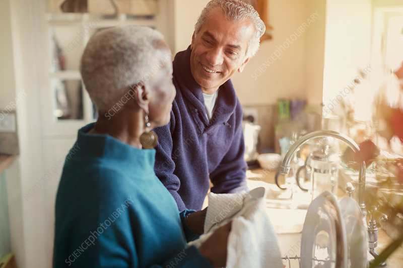 Senior couple talking and doing dishes in kitchen