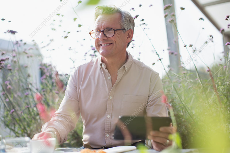 Smiling senior man using tablet on sunny patio
