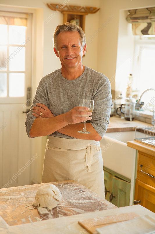 Senior man drinking wine and baking in kitchen
