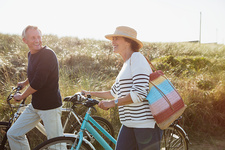 Mature couple walking bicycles grass path