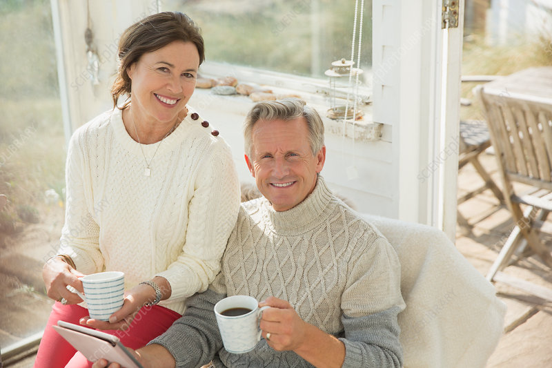 Mature couple using tablet and drinking coffee