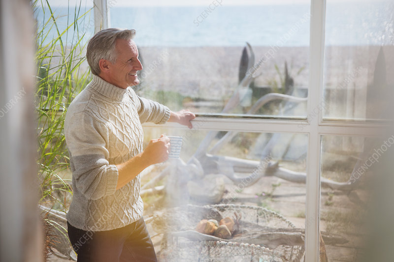 Mature man drinking coffee in sunny porch