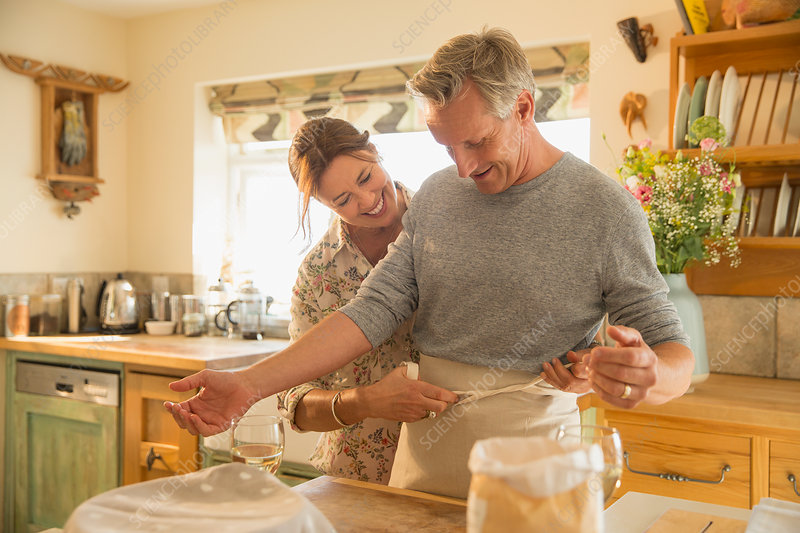 Playful mature couple baking