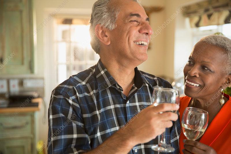 Laughing senior couple drinking white wine