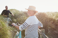 Portrait mature woman walking bicycle grass path