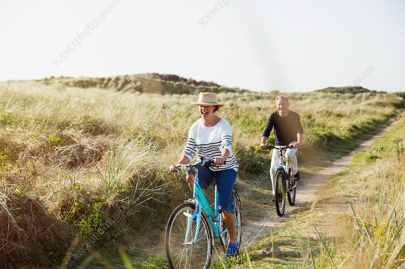 Mature couple riding bicycles grass path