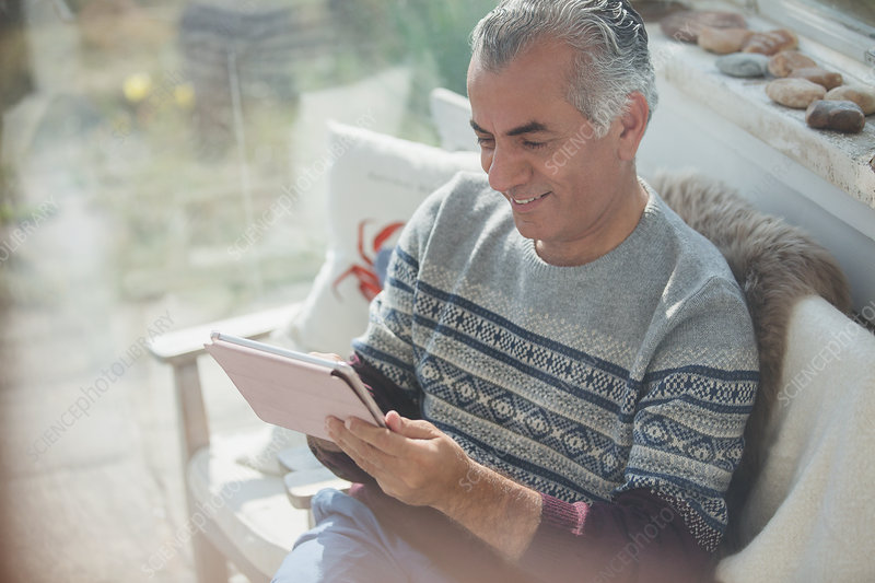 Senior man using digital tablet on sun porch