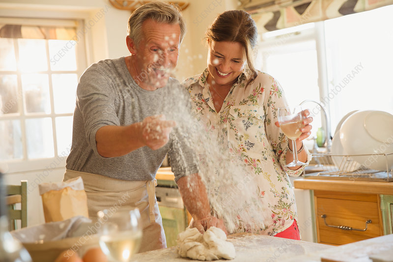 Playful mature couple baking