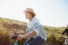 Playful mature woman riding bicycle grass path