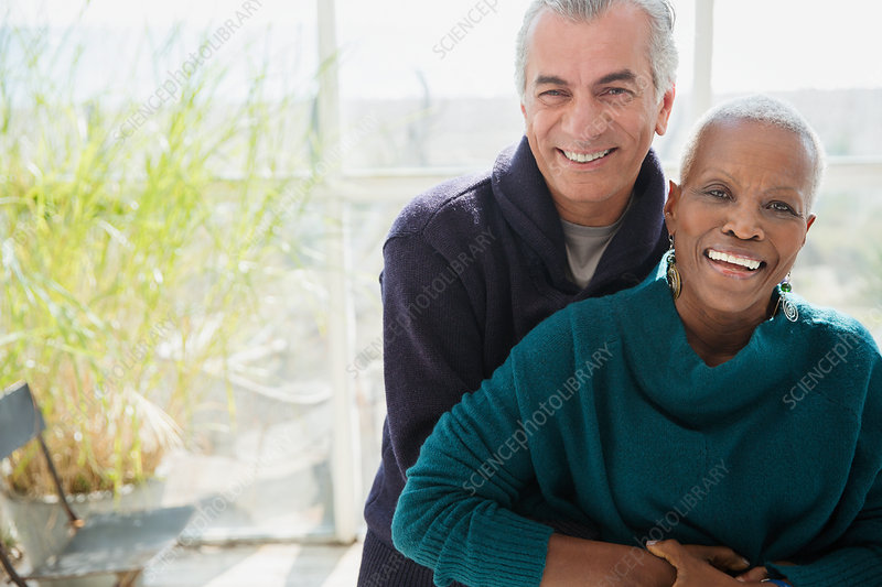 Portrait senior couple hugging on sun porch