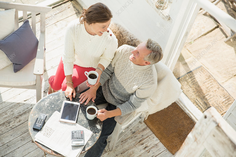 Mature couple drinking coffee and using tablet