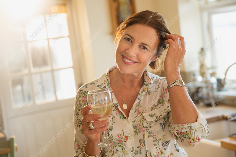 Mature woman drinking white wine in kitchen