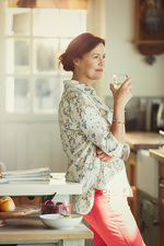 Pensive mature woman drinking wine in kitchen