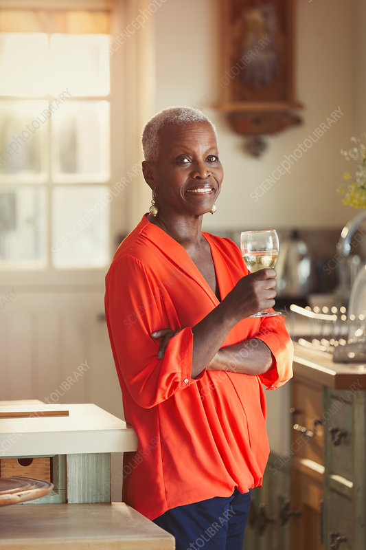 Portrait senior woman drinking wine in kitchen