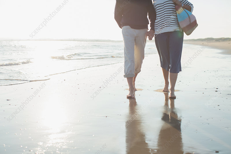 Barefoot mature couple walking, holding hands