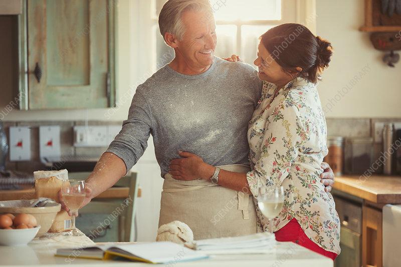 Affectionate mature couple hugging, baking