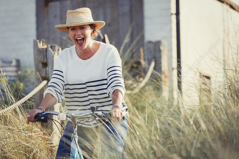 Mature woman riding bicycle on beach grass path