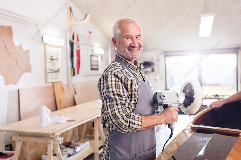 Senior male carpenter using a buffer sander