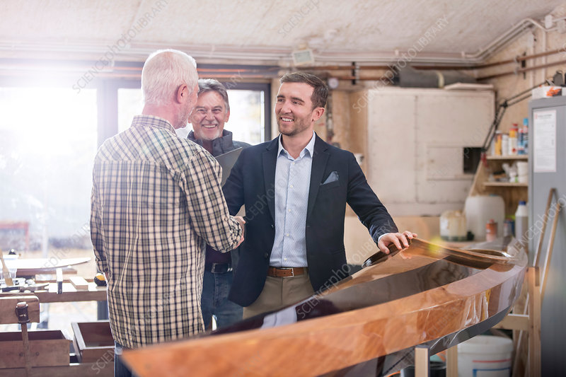Male carpenters handshaking with customer