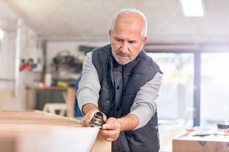Focused senior male carpenter using jack plane