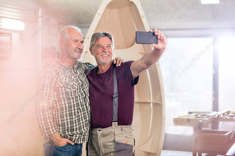 Carpenters with camera phone taking selfie