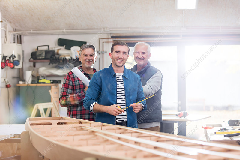 Portrait male carpenters working at wood boat