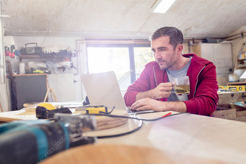 Male carpenter drinking tea and working at laptop