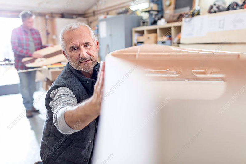 Male carpenter examining, touching wood boat