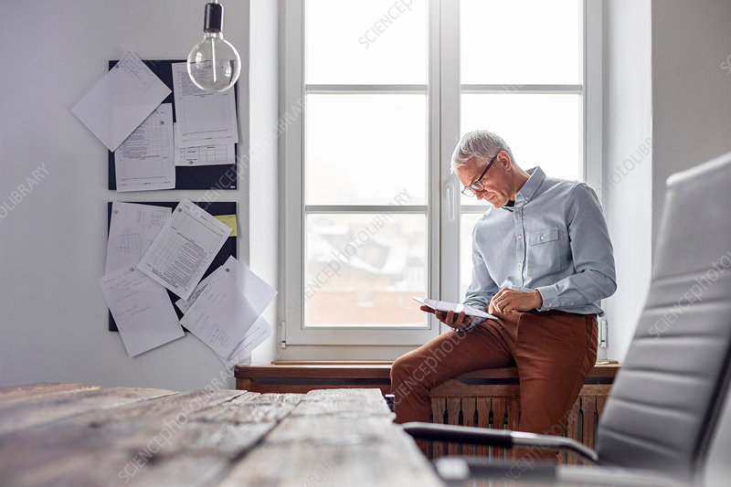 Businessman using tablet in office window