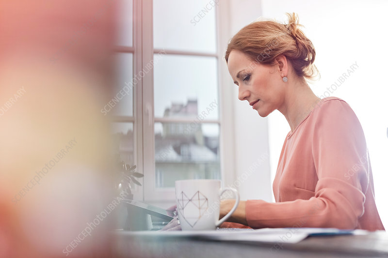 Serious, focused businesswoman working at tablet