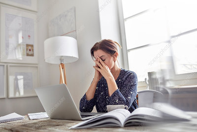 Businesswoman at laptop with head in hands