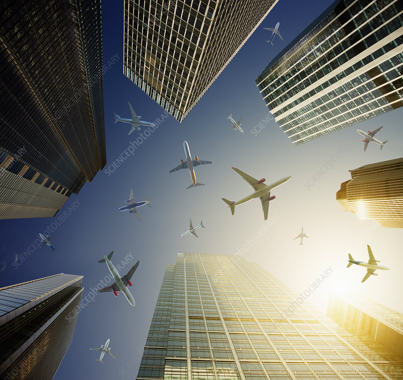 Airplanes in blue sky above highrise buildings