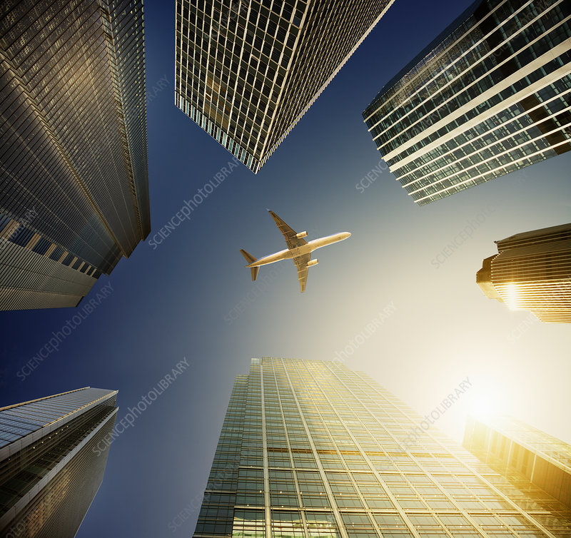 Airplane flying over highrise buildings