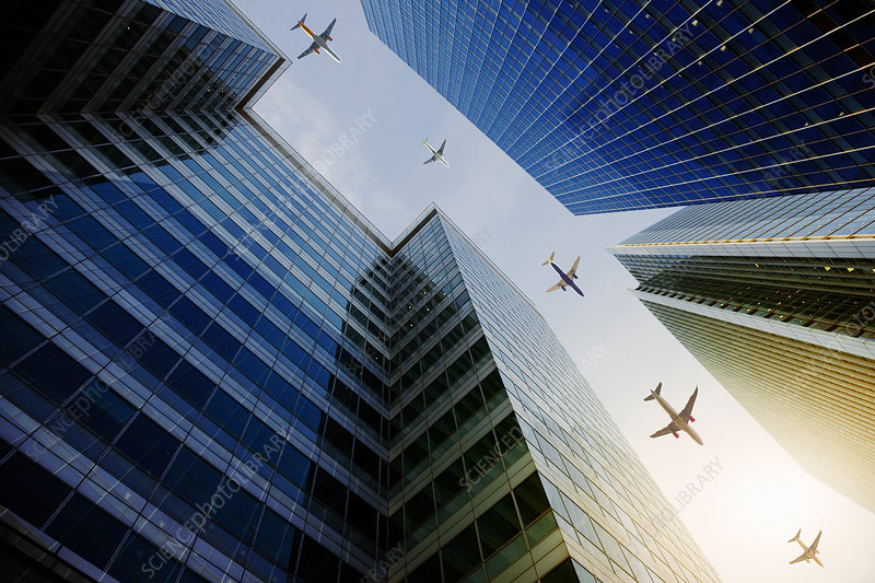 Airplanes flying in a row over highrise buildings