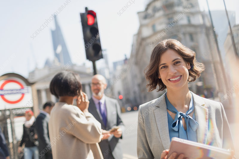 Portrait, businesswoman on sunny urban city street