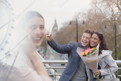 Enthusiastic couple taking selfie, London, UK