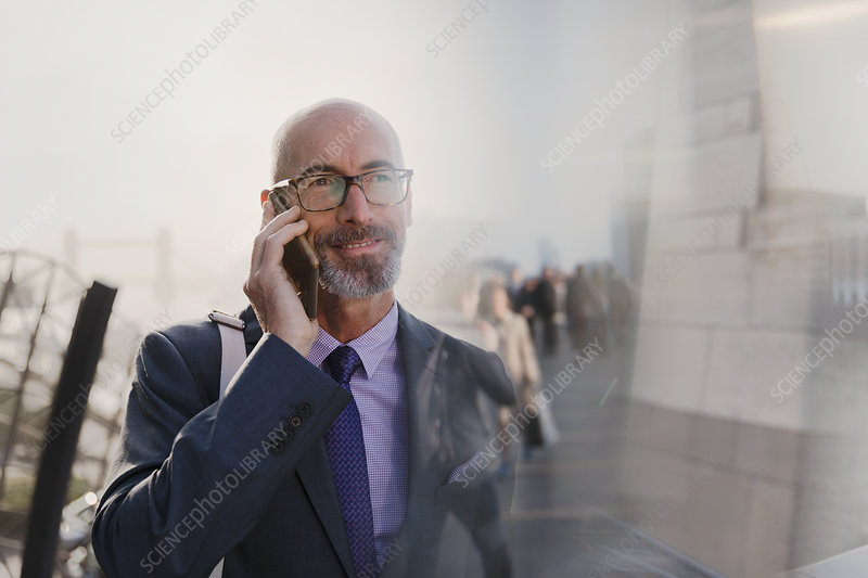 Businessman talking on cell phone on urban street
