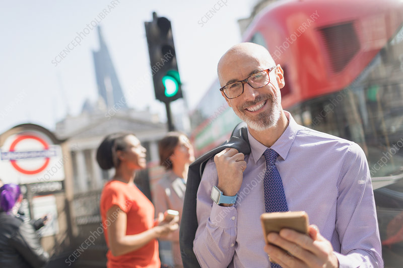 Portrait businessman with cell phone, London, UK