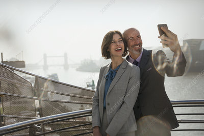Business couple taking selfie, London, UK