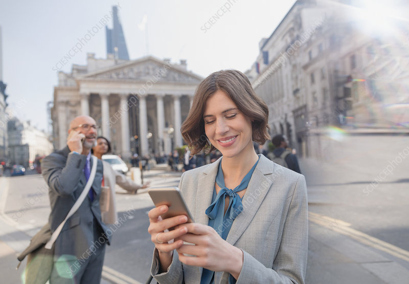 Businesswoman texting with cell phone, London, UK