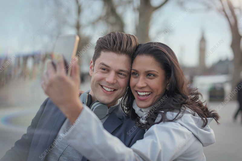 Smiling couple taking selfie in urban park