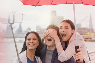 Tourists with umbrella taking selfie, London, UK