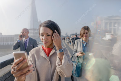 Businesswoman using cell phone, London, UK
