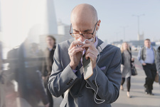Businessman blowing nose