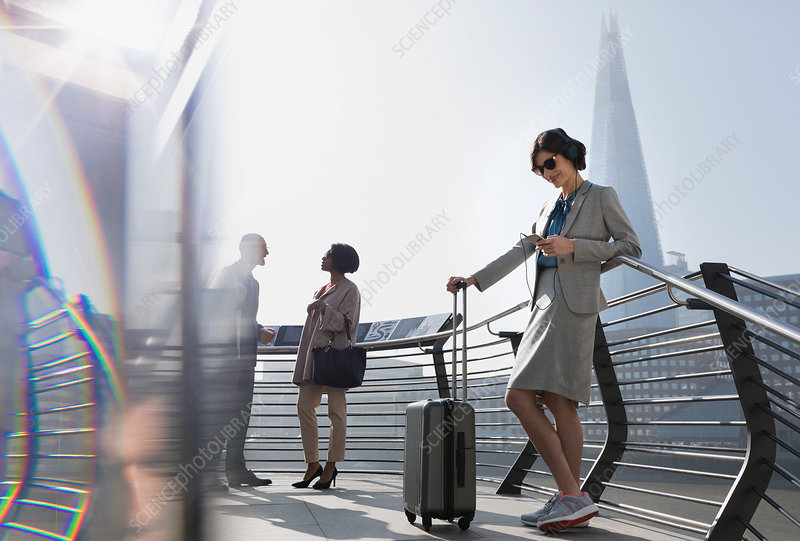 Businesswoman with suitcase, London, UK